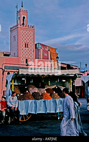 Stall selling fruit and nuts in Djemma el Fna Marrakesh Morocco kasbah mosque in background couple in local dress - Stock Photo
