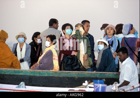 Japanese tourists in a boat on the Ganges wearing face masks - Stock Photo