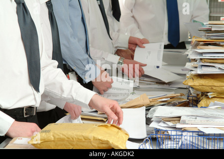 Men opening and sorting mail in the postroom of an office. - Stock Photo