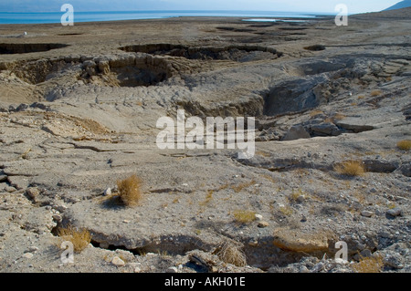 Israel Dead Sea Sink Holes Natural phenomenon due to the receding of the Dead Sea level wide view with sink holes - Stock Photo