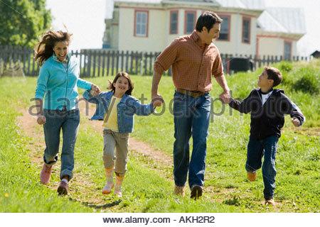 Family running on field - Stock Photo