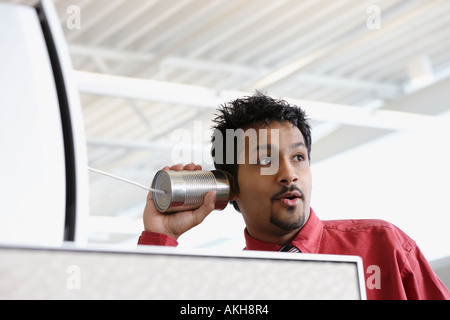 Man using a tin can telephone - Stock Photo