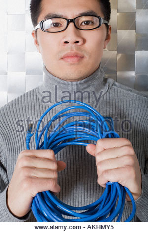 Man holding network cable - Stock Photo