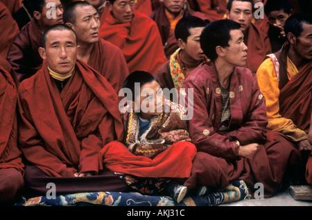 Nyingma monks watch the Buddhist Cham Dances Katok Dorjeden Monastery Kham E Tibet Sichuan Province China - Stock Photo