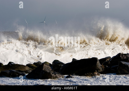 Crashing wave on rocks at Great Yarmouth during storm force winds, with offshore wind farm in distance - Stock Photo