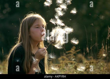 Girl dispersing Milkweed seeds USA - Stock Photo