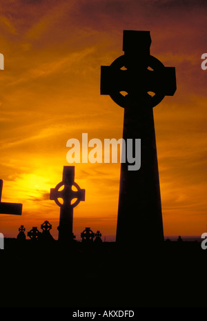 Two Celtic Crosses are silhouetted against golden sunset light in an Ancient Cemetery. County Clare, Ireland - Stock Photo