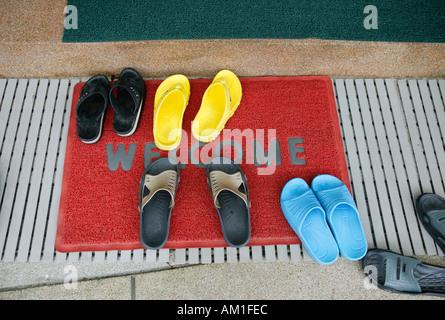 Welcome mat in front of door - Stock Photo