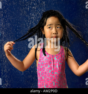 A little girl gets wet with a light shower or rain and it disturbs her hair as evident in her body language and - Stock Photo