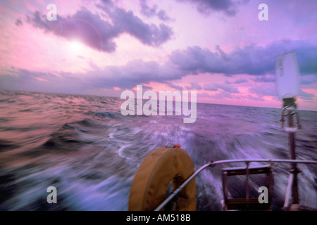 looking out astern from the cockpit of sailboat underway on a blue water passage - Stock Photo