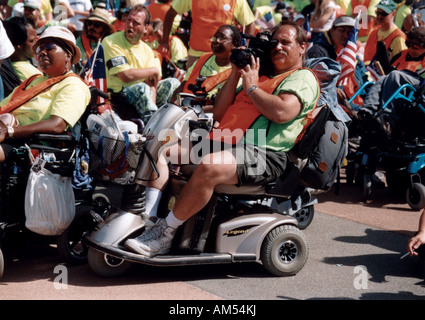 Man with disability, utilizing a scooter for mobility, filming parts of the ADAPT March on Washington Disability - Stock Photo