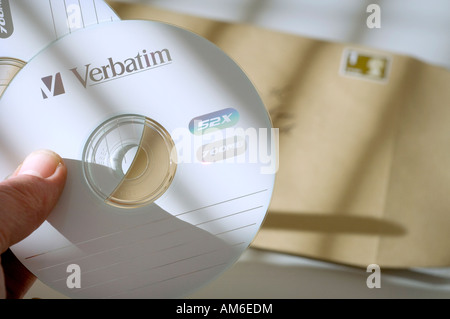 Two computer data discs being put in an envelope. Picture by Jim Holden. - Stock Photo