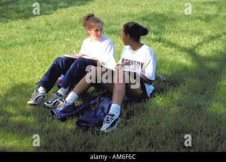 Friends age 14 studying together on grass. Minnetonka Minnesota USA - Stock Photo
