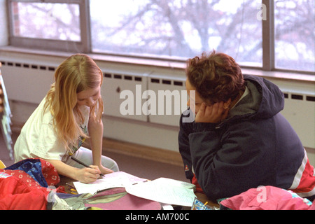 Mentor and child studying in after school reading program age 18 and 9. St Paul Minnesota USA - Stock Photo