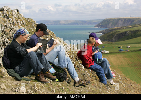 Tourists hikers walkers rest on the clifftop above Mwnt picnic read travel guides maps Cardigan bay Mid Wales Irish - Stock Photo