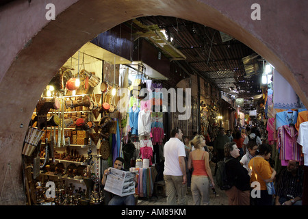 Tourists in a souk in the old part of town, Marrakech, Morocco - Stock Photo