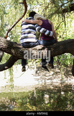 Couple sitting in a tree by a lake. - Stock Photo