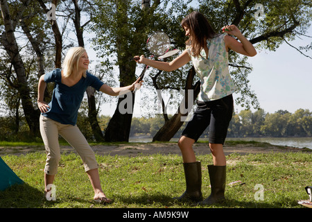 Two women play fighting with badminton racquets and laughing at campsite. - Stock Photo