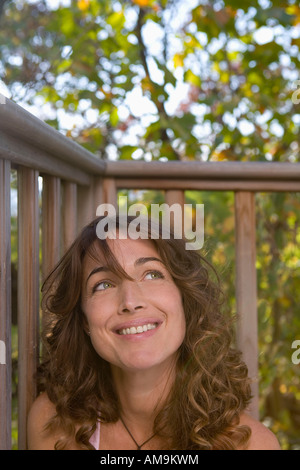 Woman sitting on balcony smiling. - Stock Photo