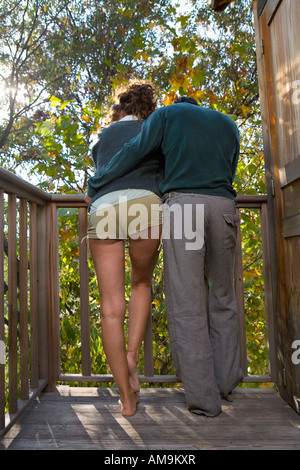 Couple outdoors on balcony being affectionate. - Stock Photo