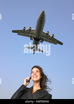Woman on cellular phone smiling with plane flying overhead. - Stock Photo