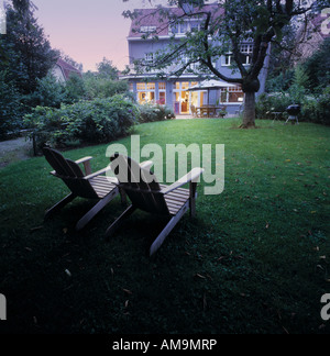 Two lawn chairs sitting on a lawn with a large house in the background. - Stock Photo