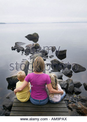 Woman with young boy and young girl sitting on a dock by a lake. - Stock Photo