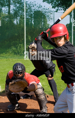 A baseball batter in front of a baseball catcher and umpire - Stock Photo