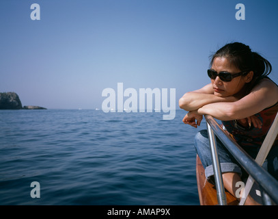 A woman sitting on a boat deck contemplation - Stock Photo