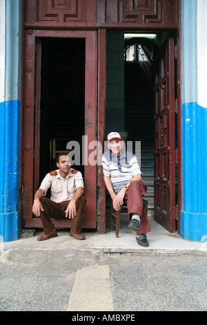 Cuba Havana two people sitting in front of a house entrance - Stock Photo