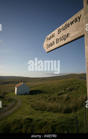 A Stock Photograph of a Sign for a Footpath and a House on top of the Pennines in Cumbria UK - Stock Photo