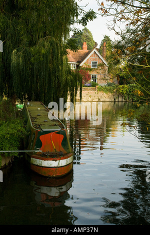 Old narrow boat moored in a quiet back water above the weir at Goring and Streatley on the river Thames in Oxfordshire - Stock Photo