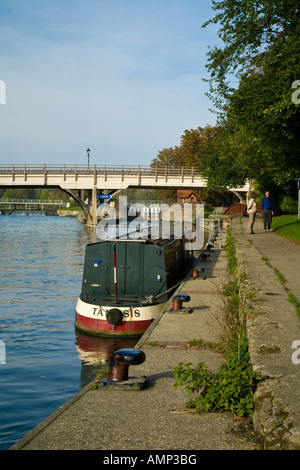 Narrow boat moored on towpath below the River Thames weir and road bridge at Goring and Streatley in Oxfordshire - Stock Photo