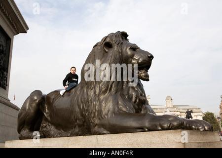 UK London Trafalgar Square young boy sat on Landseers Lion at base of Nelsons Column - Stock Photo