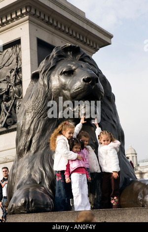 UK London Trafalgar Square children posing for photograph by Landseers Lions at base of Nelsons Column - Stock Photo