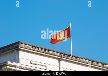 The Montenegrin flag flying on top of a building, red with a golden double headed eagle. Podgorica capital. Montenegro, - Stock Photo