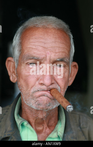 Cuba Cienfuegos January 2006 Old man in front of his door with a cigar in his mouth - Stock Photo