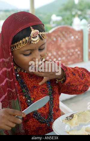 Portrait of a young Rajasthani girl in traditional dress eating a pancake, Rajasthan (India) - Stock Photo