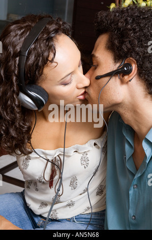 Portrait of a couple kissing while wearing headphones and ear pieces - Stock Photo
