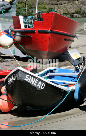 An old style fishing currach named Sinead and a larger red boat both stranded on the sandy bottom - Stock Photo