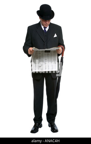 Businessman in bowler hat and three pice pinstripe suit reading a financial newspaper - Stock Photo