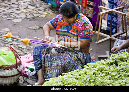GUATEMALA ANTIGUA Cakchiquel Mayan woman wearing traditional huipil and corte using a backstrap loom to weave textiles - Stock Photo