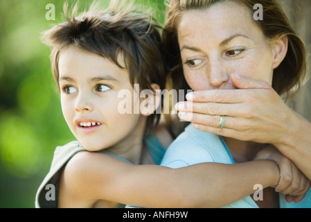 Mother and son, woman holding boy on back, whispering to him - Stock Photo