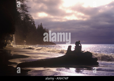 Person sitting on a log watching a storm roll inat Mystic Beach on the Juan de Fuca marine trail, British Columbia, - Stock Photo