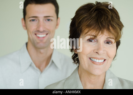 Senior woman in front of adult son, both smiling at camera, focus on foreground - Stock Photo