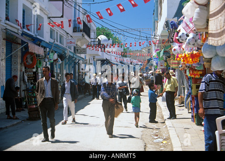 Local shoppers passing along in front of the shops strung about with colourful goods for sale on the Rue Kheireddine - Stock Photo
