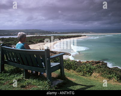 BENCH on LOOKOUT ROCKS a lady looking down on Lookout Beach Plettenberg Bay South Africa - Stock Photo