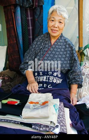 Japan, Honshu Island, Kyoto Prefecture, Kyoto City. Elderly Woman selling Kimonos at a monthly flea market at Toji - Stock Photo