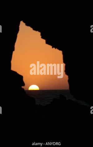 sunset inside the pedra furada bored rock beach main attraction in the beautiful fisherman village of Jericoacoara - Stock Photo