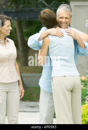 Woman hugging man as second woman watches smiling - Stock Photo